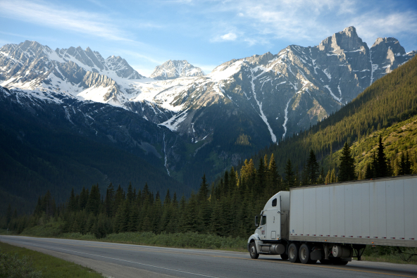 Truck on road, mountains in background